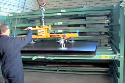 An operator retrieves individual sheets of steel from a Roll-Out Sheet Rack with a vacuum lifter.